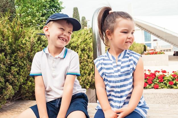 Kindermode-konzept. jugendlich junge und mädchen, die am park sitzen