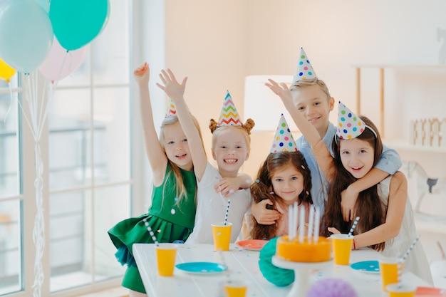 Kinderparty und feierkonzept. gruppe von kleinen kinderfreunden machen foto zusammen, heben die arme und lächeln fröhlich, haben geburtstagsfeier