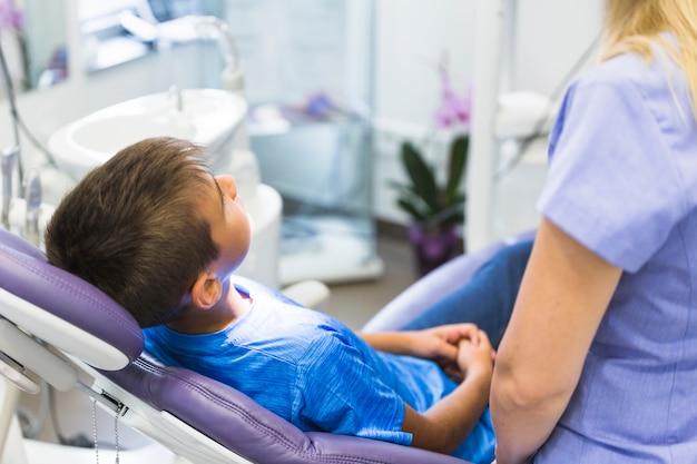 Kinderpatient, der auf zahnmedizinischem stuhl in der klinik sich lehnt