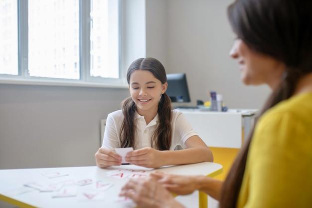 Kinderpsychologie. beteiligt lächelndes langhaariges mädchen, das am tisch mit alphabetkarten und frauenpsychologin spielt