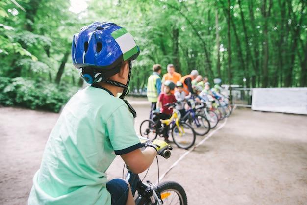Kinderradfahren. junge in einem helm gegen radfahrer, die am start sind. kindersport