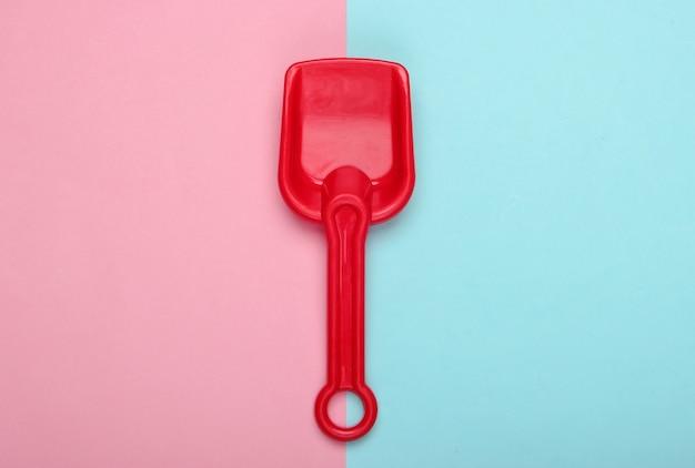 Kinderschaufel für einen sandkasten oder strand auf blauem rosa