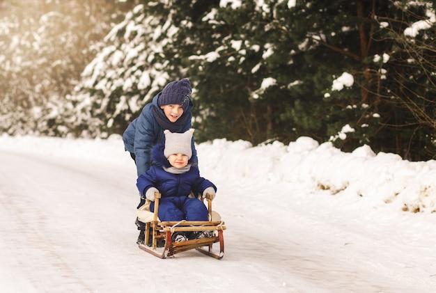 Kinderschlitten im winter im wald. bruder und schwester zusammen