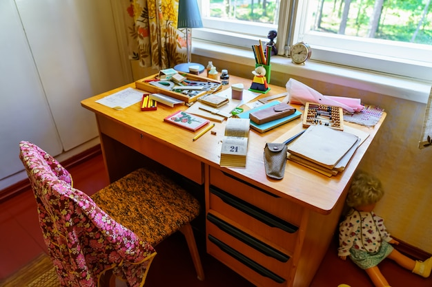 Kinderschreibtisch zum studieren mit sehr alten materialien und utensilien aus vergangenen zeiten.
