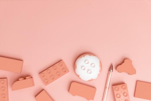 Kinderspielwaren auf rosa hintergrund mit draufsicht der spielwarenebenenlage mit leerer mitte
