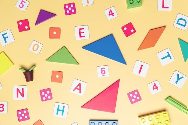 Kinderspielzeug auf gelber draufsichtebene des hintergrundes legen mit kopienraum