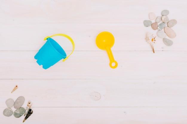 Kinderspielzeug für sandkasten mit muscheln auf heller oberfläche