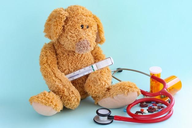 Kinderspielzeug mit thermometer, stethoskop und medizinischen pillen auf blauem hintergrund. erhöhte körpertemperatur im kinderkonzept