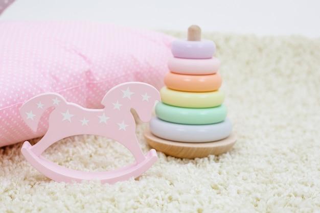 Kinderspielzeug regenbogenfarbene pyramide und rosa spielzeugpferd