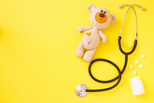 Kinderspielzeug teddybär amigurumi mit stethoskop auf gelb