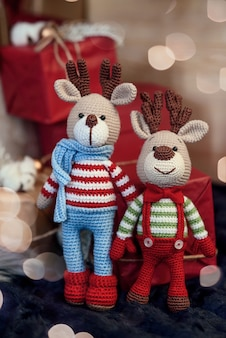 Kinderspielzeug. zwei stilvolle amigurumi-hirsche in gestreiften pullovern, schal und schmetterlingsbindung stehen neben weihnachtsgeschenken.