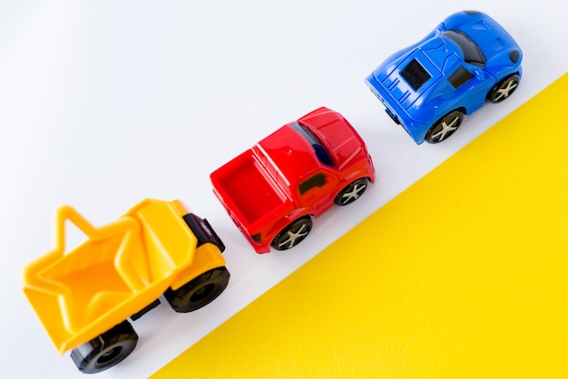 Kinderspielzeugautos auf weiß und gelb.