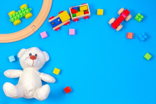 Kinderspielzeughintergrund mit teddybär, hölzernem zug und bunten blöcken. draufsicht