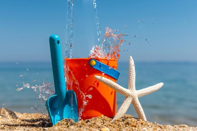 Kinderstrandspielzeug eimer, spaten und seesterne auf sand