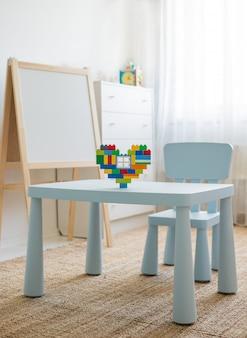Kindertisch mit spielzeug. mehrfarbiger designer in form eines herzens auf dem tisch.