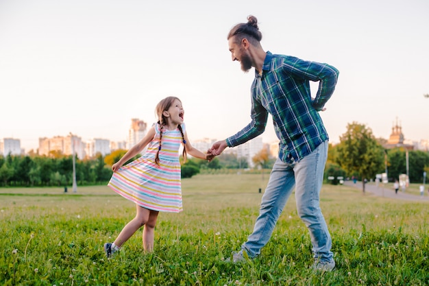 Kindertochter des kleinen mädchens, die ihre vaterhand im park hält