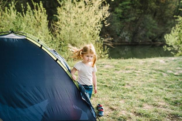 Kindertourismus. glückliches kind mädchen in einer kampagne in einem zelt. familiensommerferien in der natur.