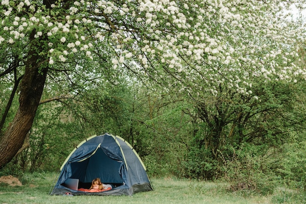 Kindertourismus. kind mit laptop im zelt auf dem campingplatz. mädchen, das karikatur auf gadget beobachtet. kind mädchen in einer kampagne in einem zelt. familiensommerferien in der natur.