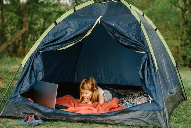 Kindertourismus. kind mit laptop im zelt auf dem campingplatz.