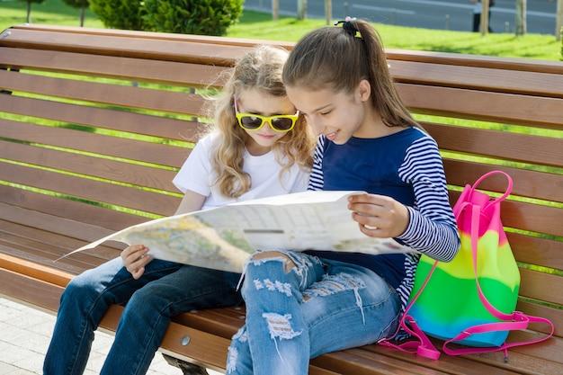 Kindertouristen mit karte der stadt auf der bank