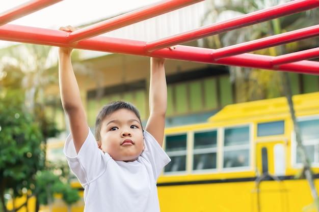 Kinderübung für gesundheits- und sportkonzept. glücklicher asiatischer studentenkindjunge, der von einer stahlstange am spielplatz spielt und hängt.