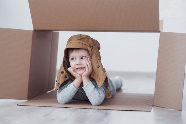 Kindervorschülerjunge, der innerhalb des papierkastens spielt. kindheit, reparaturen und neues haus