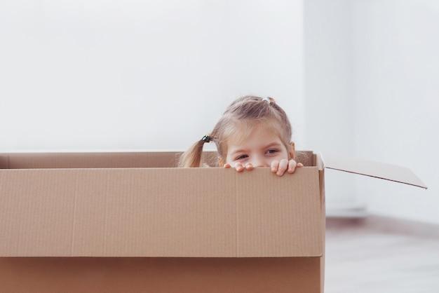 Kindervorschülerjunge, der innerhalb des papierkastens spielt. kindheit, reparaturen und neues hauskonzept