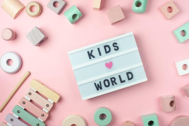 Kinderwelt - text auf anzeige leuchtkasten und spielzeug für kleine kinder auf rosa hintergrund. flach liegen. farbiges pastellfarbenes holzspielzeug, xylophon.