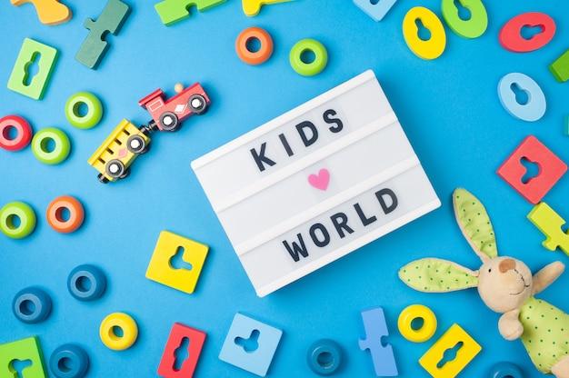 Kinderwelt - text auf display-leuchtkasten und spielzeug für kleine kinder auf blauem hintergrund. flach liegen. farbiges holzspielzeug, hase und zug.