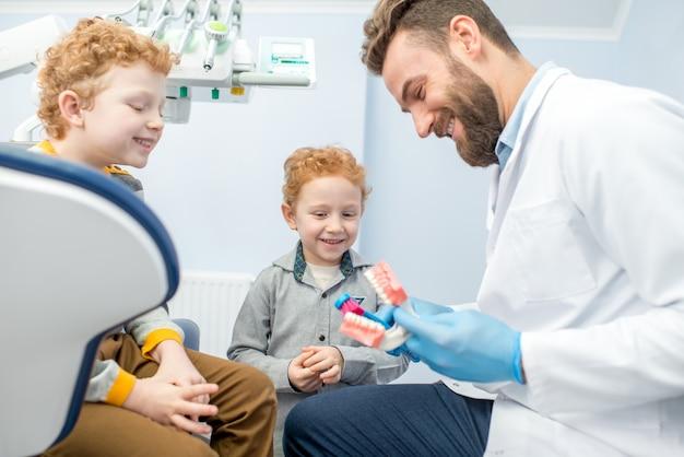 Kinderzahnarzt, der den jungen zeigt, wie man in der zahnarztpraxis zähne am künstlichen kiefer putzt