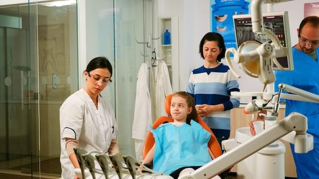 Kinderzahnarzt, der den zahnreinigungsprozess von kindern erklärt, während der assistent sterilisierte werkzeuge für die untersuchung vorbereitet. krankenschwester und arzt arbeiten in einer modernen stomatologischen klinik zusammen