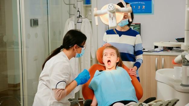 Kinderzahnarzt und assistentin, die mädchenpatienten in der modernen stomatologischen klinik behandelt. krankenschwester und arzt tragen schutzmasken, die die zähne des kindes in der zahnarztpraxis reinigen, die mit offenem mund auf einem stuhl liegen chair