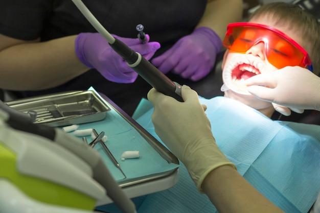 Kinderzahnheilkunde. kinderzahnarztuntersuchung milchzähne. emotionen eines kindes in einem zahnarztstuhl. kleiner junge in orangefarbener schutzbrille und kofferdamm.