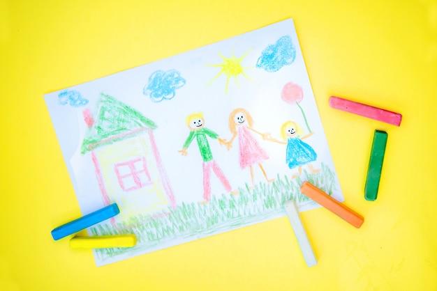 Kinderzeichnung einer familie mit farbigen buntstiften auf einem gelben
