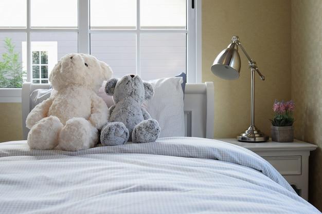 Kinderzimmer mit puppen und kissen auf bett und nachttischlampe