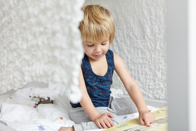 Kindheit und freizeit. entzückender süßer kleiner blonder junge im schlafanzug, der auf seinem bett vor offenem buch sitzt, seinen zeigefinger zeigt, bilder zeigt, konzentriert aussieht.