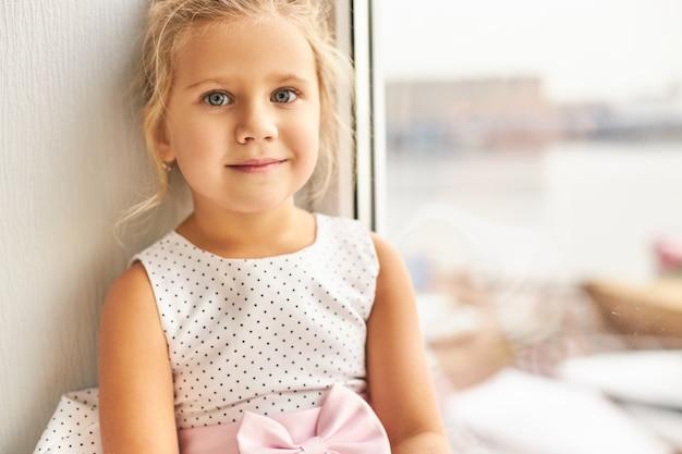 Kindheit und unschuldiges konzept. porträt des charmanten niedlichen kleinen mädchens mit gesammeltem hellem haar und großen schönen augen, die am fenster sitzen, glücklichen gesichtsausdruck und lächelnd haben