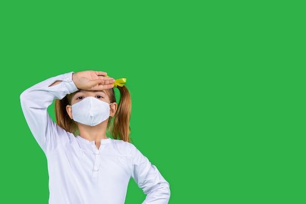 Kindheit unwohlsein ein mädchen in einer medizinischen maske hält ihre hand in der nähe ihres kopfes grün isoliert