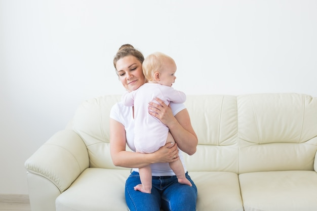 Kindheits-, familien- und mutterschaftskonzept - mutter, die süßes baby hält