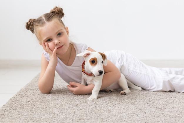 Kindheits-, haustier- und hundekonzept - kleines kindermädchen, das auf dem boden mit welpen aufwirft