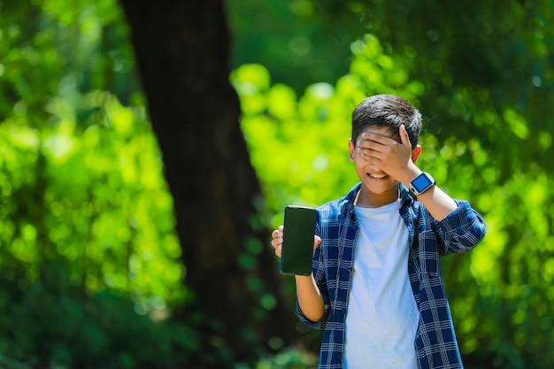 Kindheits-, technologie- und personenkonzept - indischer niedlicher schuljunge, der smartphone mit leerem bildschirm zeigt