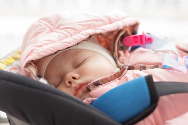 Kindheits- und sicherheitskonzept - säuglingsbaby, das im kinderautositz schläft.