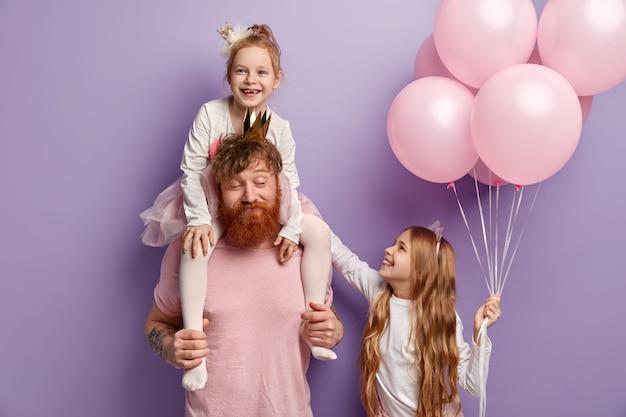 Kindheits- und vaterschaftskonzept. rothaariger vater reitet huckepack für kleine tochter, unterhält kinder auf geburtstagsfeier. kleines kind gibt luftballons für freund, fühlt sich glücklich, isoliert
