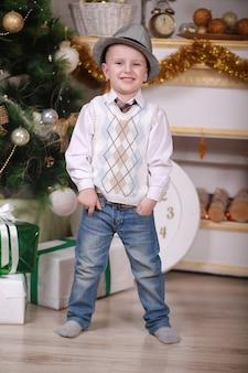 Kindheitserinnerungen. kleiner junge mit hut feiern weihnachten zu hause. jungenkind spielen nahe weihnachtsbaum. frohe und helle weihnachten. aktivität und spiel in der kindheit. familienurlaub.