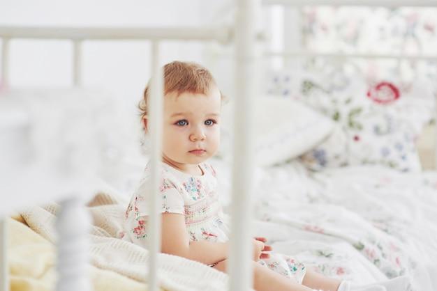 Kindheitskonzept. baby im netten kleid, das am bett spielt mit spielwaren durch das haus stationiert. weißes vintage kinderzimmer