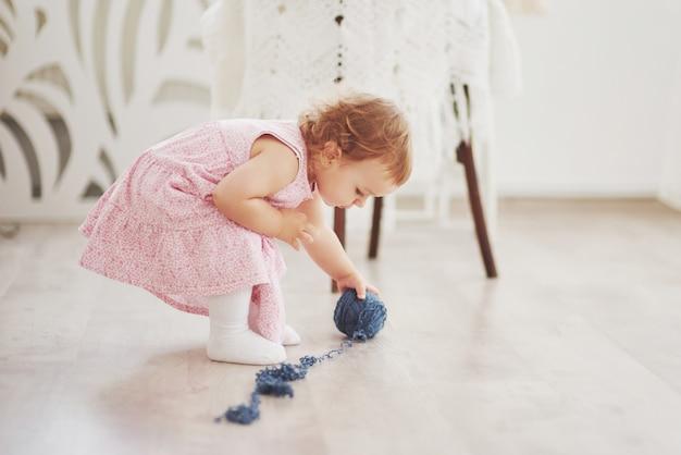 Kindheitskonzept. baby im niedlichen kleid spielen mit farbigem faden. weißes vintage kinderzimmer