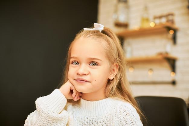 Kindheitskonzept. innenbild des schönen kleinen mädchens mit dem langen haar, das in der küche mit girlande sitzt, die weißes band und gestrickten pullover trägt, hand unter ihrem kinn hält und lächelt