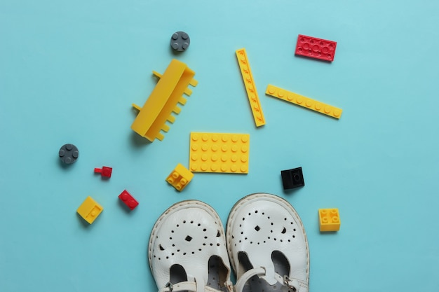 Kindheitskonzept kindersandalen spielzeugziegel