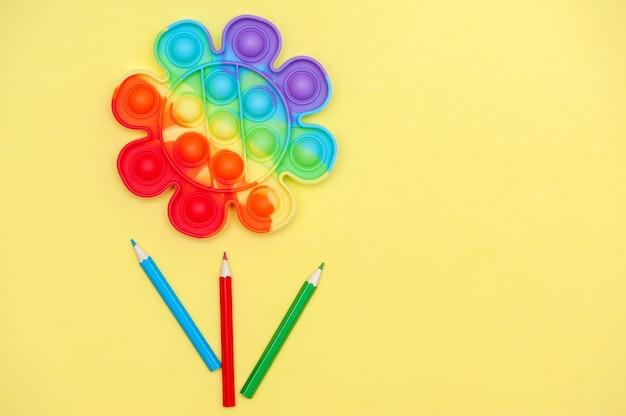 Kindheitskonzept regenbogenfarbenes spielzeug anti-stress für die finger pop it in form einer blume auf gelbem hintergrund