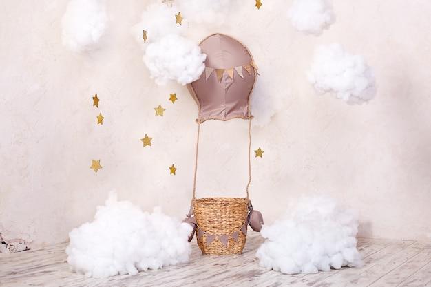 Kindheitsträume. stilvolles vintage kinderzimmer mit aerostat, luftballons und textilwolken. kinderstandort für ein fotoshooting: aerostat, ballon und wolken. innenkinderzimmer für spiele.